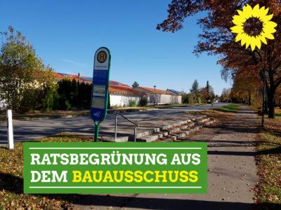 """Bushaltetelle mit Stufen ohne Rampe. Grünes Banner """"Ratsbrgrünung aus dem Bauausschuss"""" und gelbe Sonnenblume"""